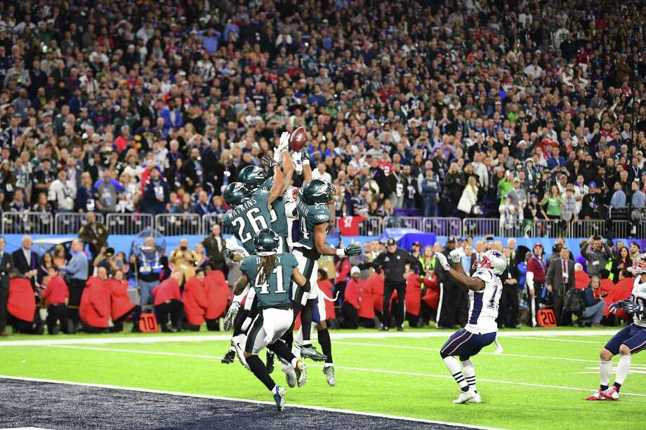 Players jump for the final throw by New England Patriots quarterback Tom Brady in Super Bowl LII against the Philadelphia Eagles at U.S. Bank Stadium in Minneapolis, Feb. 4, 2018. The Sunday night championship, in which the Philadelphia Eagles toppled the New England Patriots 41-33, attracted an overnight rating of 47.4 on NBC, according to preliminary data from the network, down about 3 percent from last year. Photo: BEN SOLOMON /NYT / NYTNS