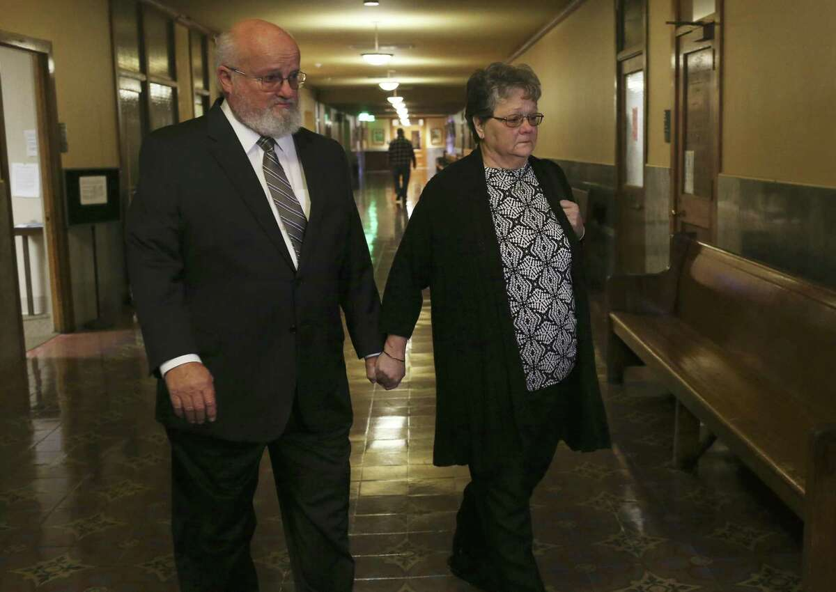 """Timothy and Sharlotte Mott enter the Bexar County 131st District Court on Monday. The Mott family is suing Robert """"Dick"""" Tips and his wife, Kristin, owner of Mission Park funeral homes, after their daughter's body went missing in 2015."""