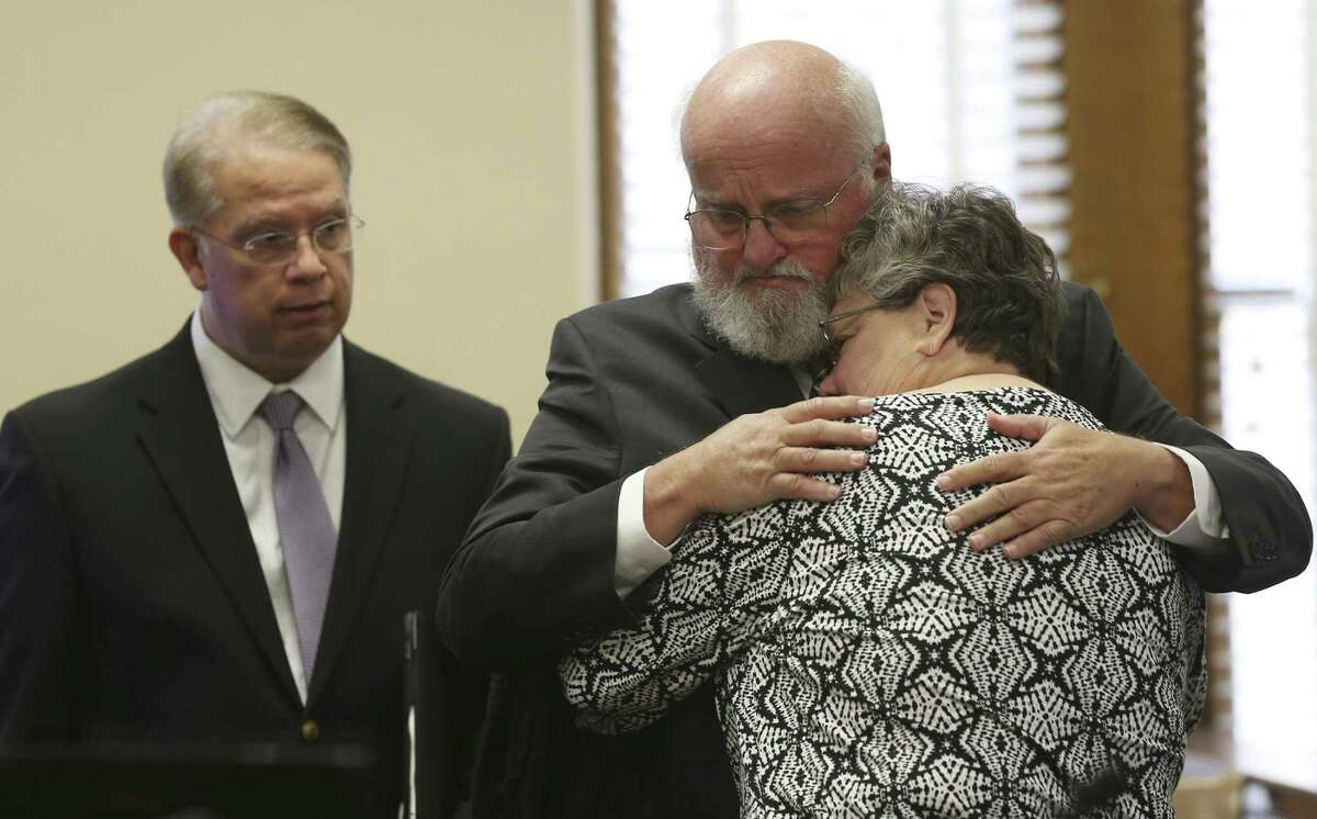 """Timothy and Sharlotte Mott hug inside the Bexar County 131st District Court on Monday. The Mott family is suing Robert """"Dick"""" Tips and his wife, Kristin, owner of Mission Park funeral homes, after their daughter's body went missing in 2015. On the left is one of their attorneys, Ron Salazar."""