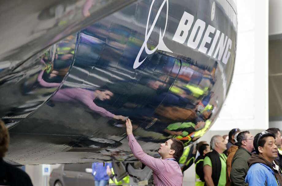 Boeing worker Paul Covaci reaches out to touch a Boeing 737 MAX 7, the newest version of Boeing's fastest-selling airplane, during a debut for employees and media of the new jet Monday, Feb. 5, 2018, in Renton, Wash. The company announced record bonuses for Washington-based employees on Tuesday. Photo: Elaine Thompson/AP