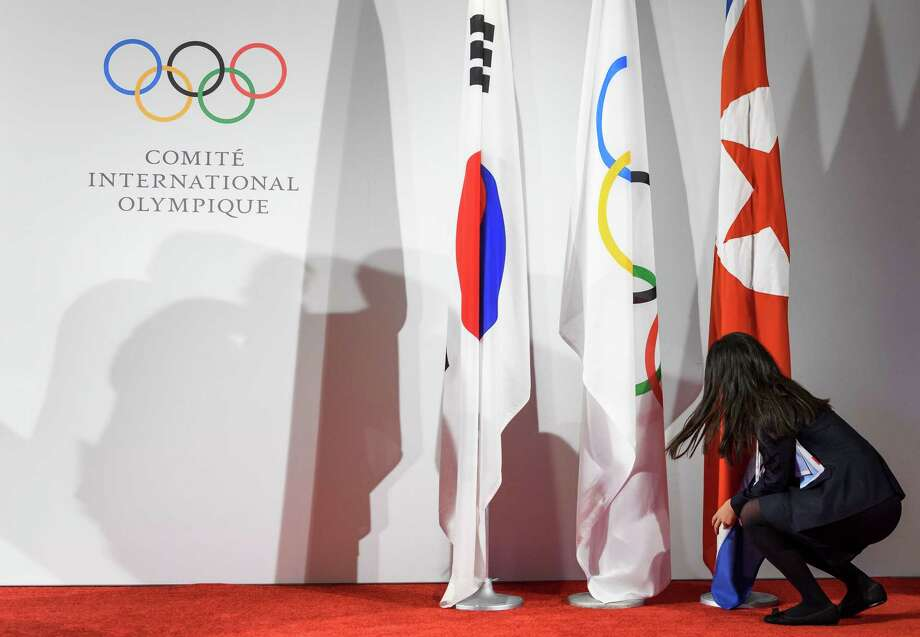 A staff of the International Olympic Committee (IOC) arranges the South Korean, IOC and North Korean flags prior to the North and South Korean Olympic Participation Meeting at the IOC headquarters on January 20 in Pully near Lausanne.(FABRICE COFFRINI/AFP/Getty Images) Photo: FABRICE COFFRINI / AFP or licensors