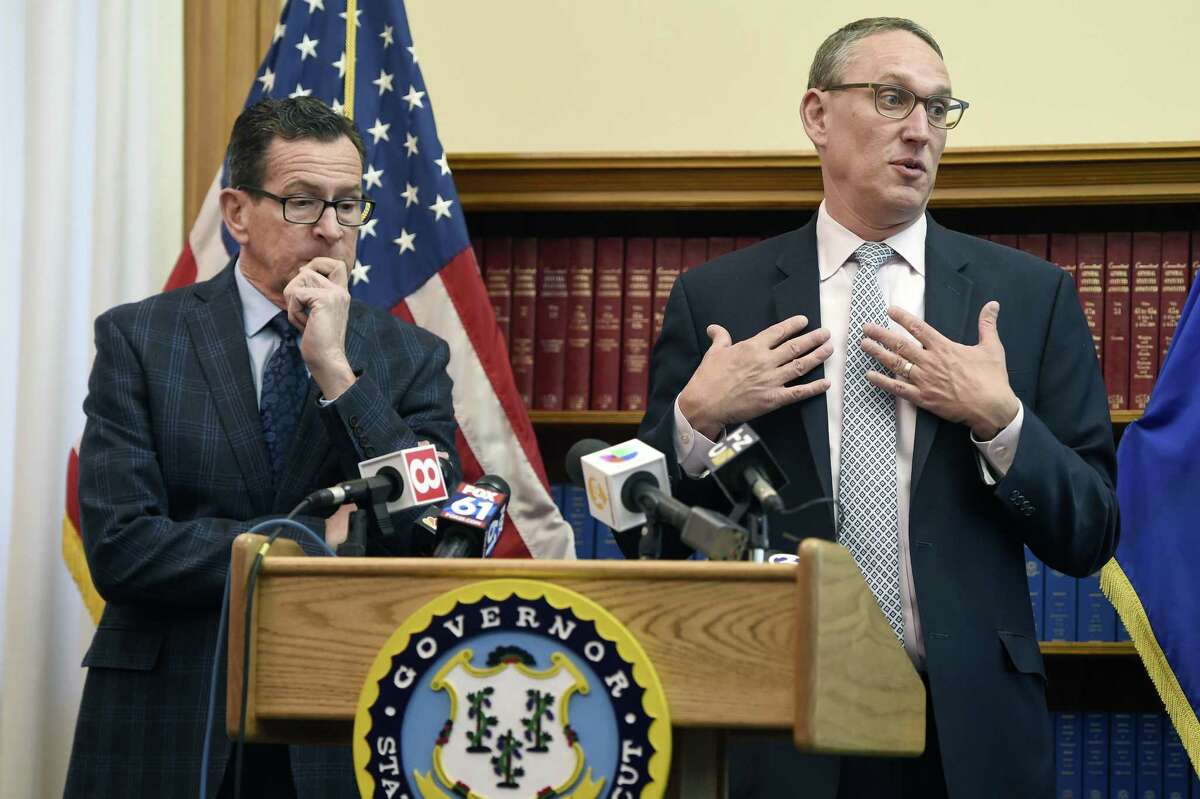 Gov. Dannel P. Malloy, left, listens as Ben Barnes, Secretary of the State of Connecticut Office of Policy and Management, right, speaks about the budget adjustments that they are proposing for the 2019 Fiscal Year during a press conference at the state Capitol Monday, Feb. 5, 2018 in Hartford, Conn. afternoon.
