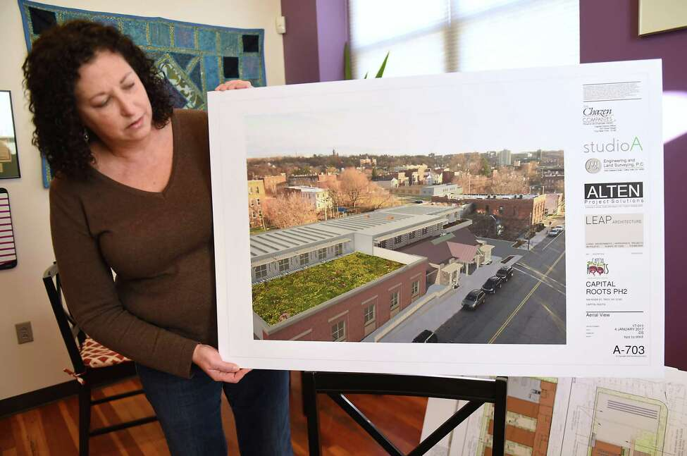Capital Roots Chief Executive Officer Amy Klein looks over expansion renderings for the Capital Roots headquarters in her office at 594 River St. on Monday, Feb. 5, 2018 in Troy, N.Y. (Lori Van Buren/Times Union)