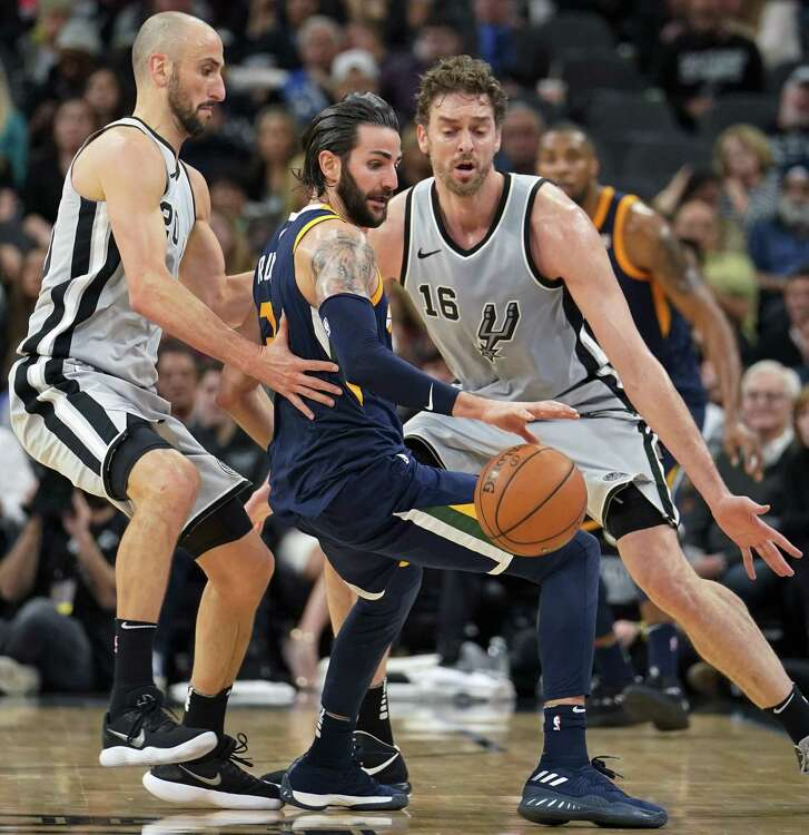 Utah Jazz' Ricky Rubio, center, loses the ball as he is guarded by San Antonio Spurs' Pau Gasol (16) and Manu Ginobili during the first half of an NBA basketball game, Saturday, Feb. 3, 2018, in San Antonio. (AP Photo/Darren Abate)