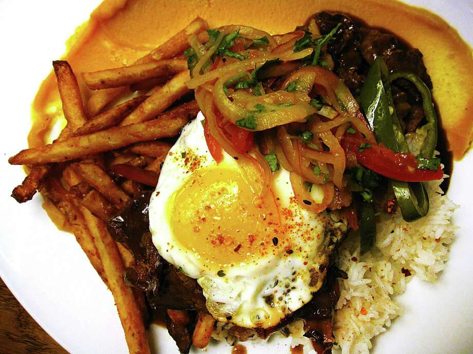 Lomo saltado combines sliced tenderloin, fries, plantain puree, rice and a fried egg at Botika at The Pearl. Photo: Mike Sutter /San Antonio Express-News