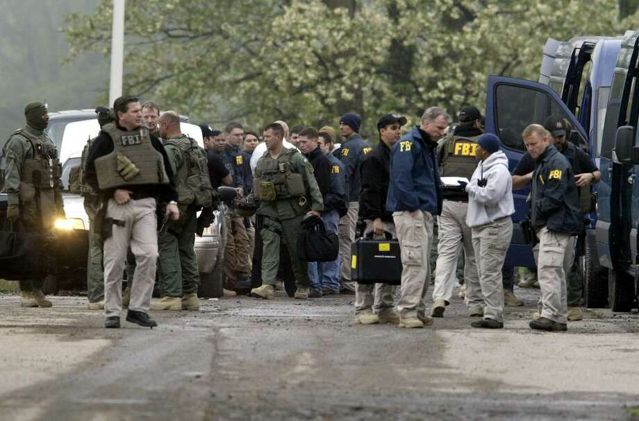 FBI agents gather Thursday outside the Armory in Newburgh after multiple law enforcement agencies raided gang hideouts. (Times Herald Record, Chet Gordon/Associated Press) Photo: Chet Gordon / Times Herald Record