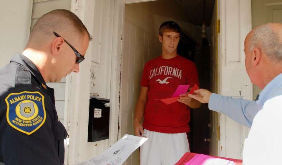 Student Jacob Roth, 19, gets safety information from officer Rick Romand, left, and UAlbany's Thomas Gebhardt. (Luanne M. Ferris / Times Union) Photo: LMF / 00005492A