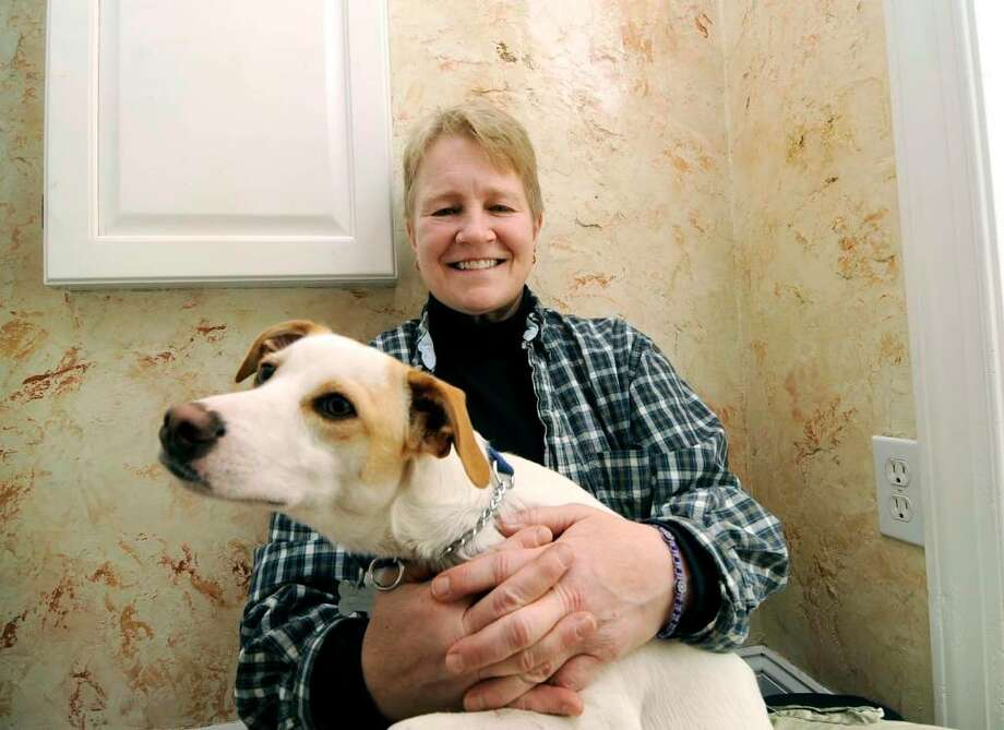Plaster artist Lori Blomstrom sits in her entryway with Giacomo, her dog. The finish on the walls behind her is an 8-layer finish called Tuscan Stone. (Allentown Morning Call) Photo: DON FISHER / THE ALLENTOWN MORNING CALL