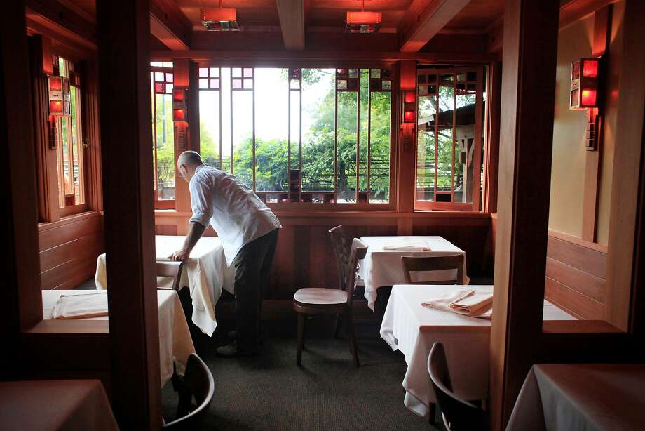 Chez Panisse waiter Gianni Benecchi sets the tables in the downstairs dining room. Photo: Mike Kepka, The Chronicle