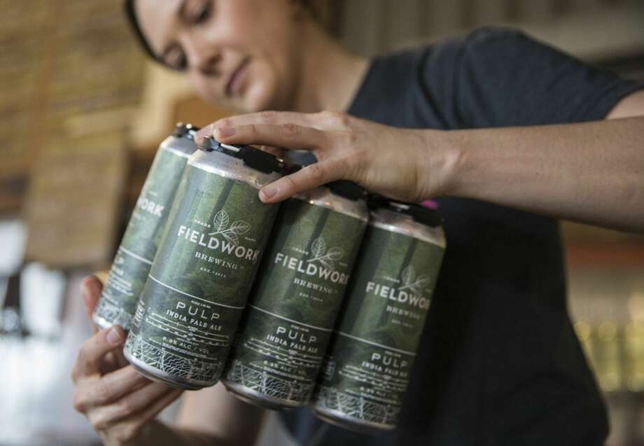 Tessa Ridgway prepares a 6-pack of Pulp IPA for a customer during a special can release at Fieldwork Brewing Company Saturday, Feb. 3, 2018 in Berkeley, Calif. Photo: Jessica Christian/The Chronicle