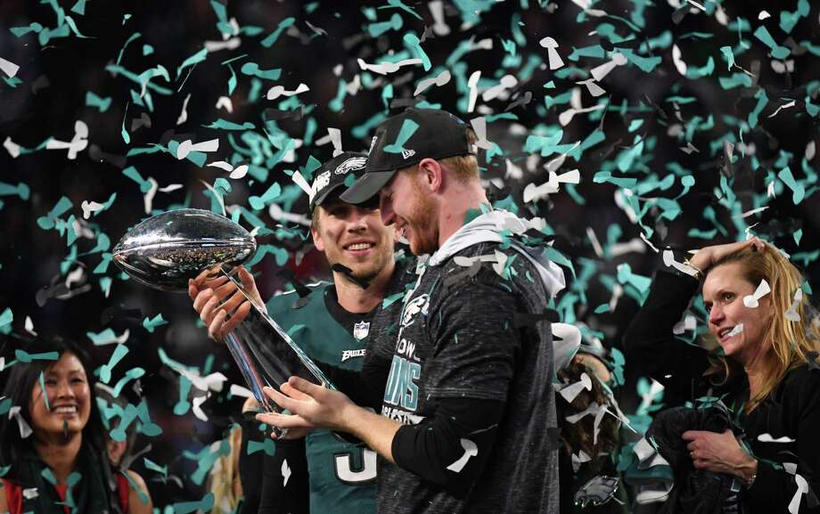 Philadelphia quarterbacks Nick Foles, left, and Carson Wentz share in the Super Bowl celebration Sunday, but only one of them can be the Eagles' starting QB next season. Photo: TIMOTHY A. CLARY, Contributor / AFP or licensors