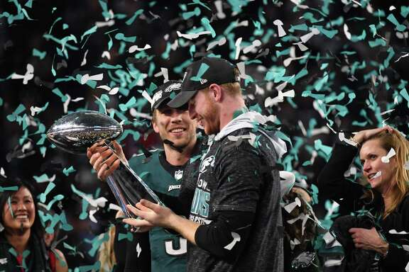 Philadelphia quarterbacks Nick Foles, left, and Carson Wentz share in the Super Bowl celebration Sunday, but only one of them can be the Eagles' starting QB next season.