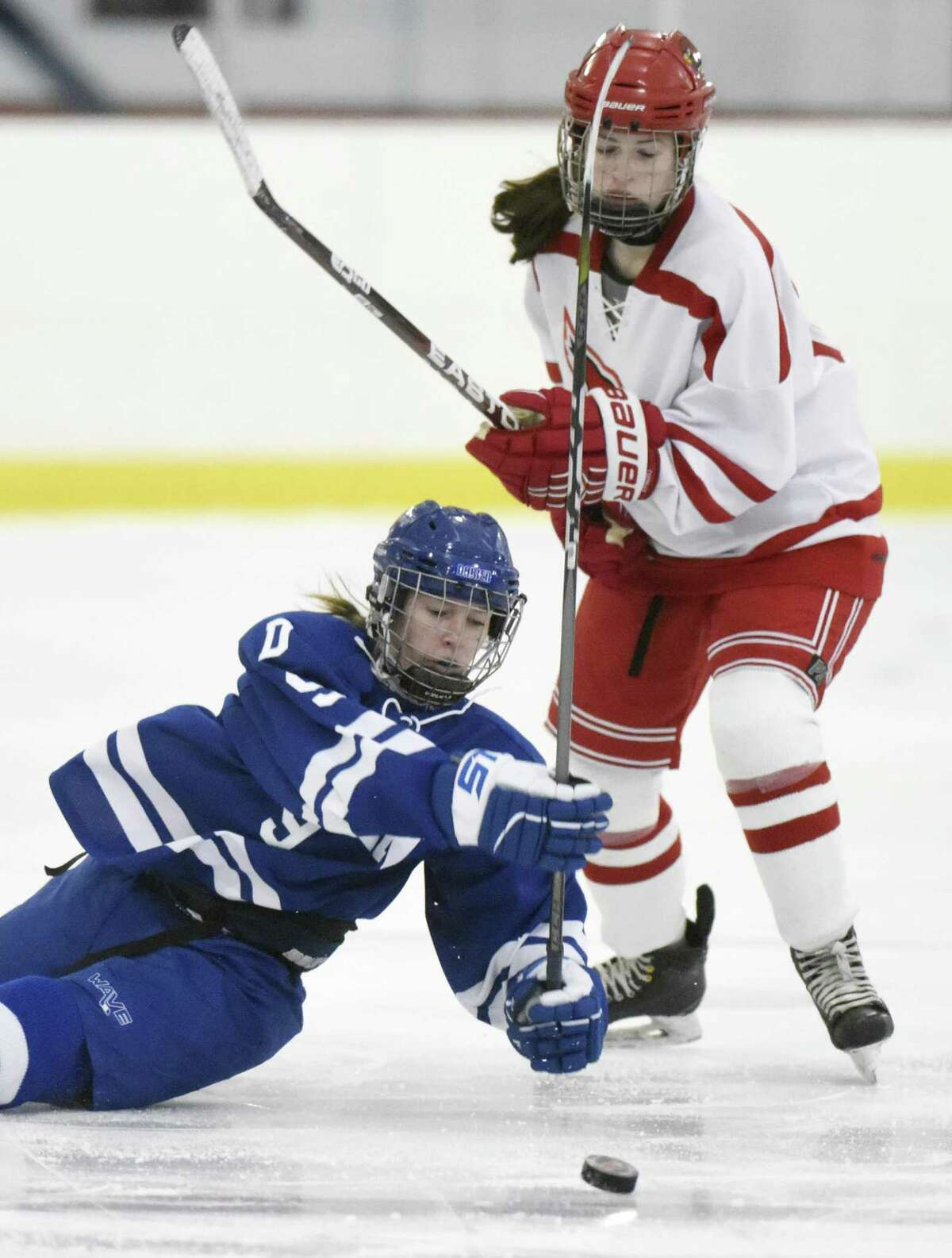 Darien's Kate Bellissimo, left, slips to the ice while battling Greenwich's Katie Piotrzkowski for the puck in the high school girls hockey game between Greenwich and Darien at Dorothy Hamill Skating Rink in Greenwich, Conn. Monday, Feb. 5, 2018.