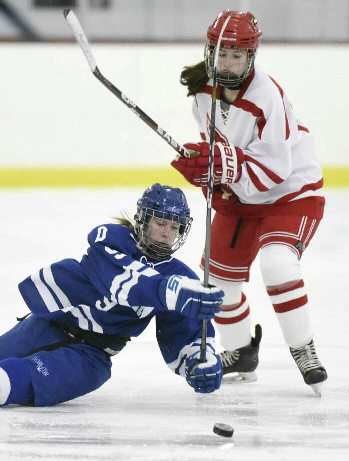 Darien's Kate Bellissimo, left, slips to the ice while battling Greenwich's Katie Piotrzkowski for the puck in the high school girls hockey game between Greenwich and Darien at Dorothy Hamill Skating Rink in Greenwich, Conn. Monday, Feb. 5, 2018. Photo: Tyler Sizemore / Hearst Connecticut Media / Greenwich Time