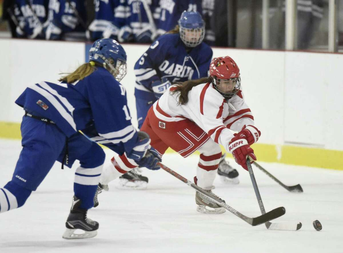 Greenwich's Paige Finneran, center, and Darien's Shea van den Broek, left, battle for posession in the high school girls hockey game between Greenwich and Darien at Dorothy Hamill Skating Rink in Greenwich, Conn. Monday, Feb. 5, 2018.