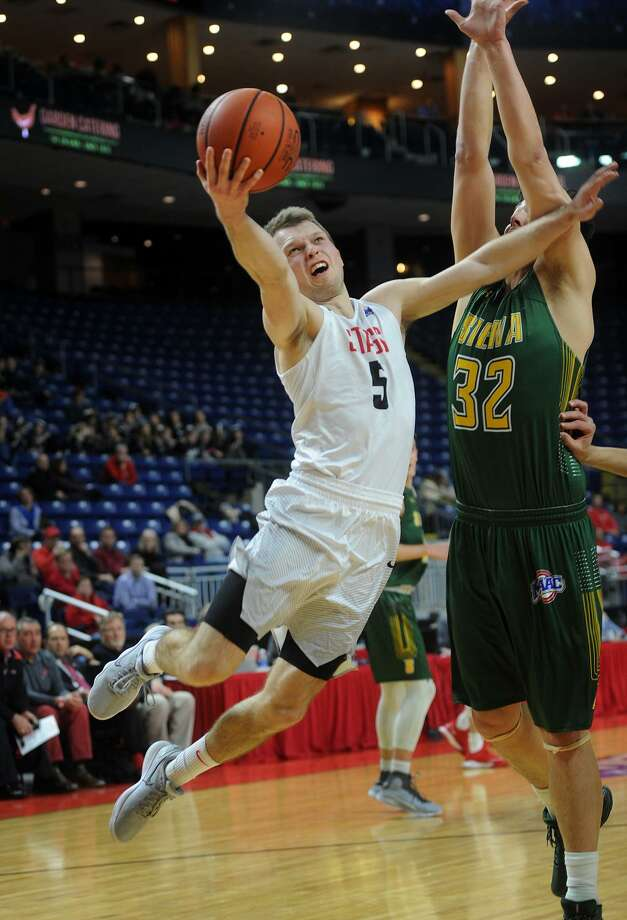 Fairfield University's Aidas Kavaliauskas drives to the basket while defended by Siena's Evan Fisher in the first half of Monday's game at the Webster Bank Arena in Bridgeport. Photo: Brian A. Pounds / Hearst Connecticut Media / Connecticut Post