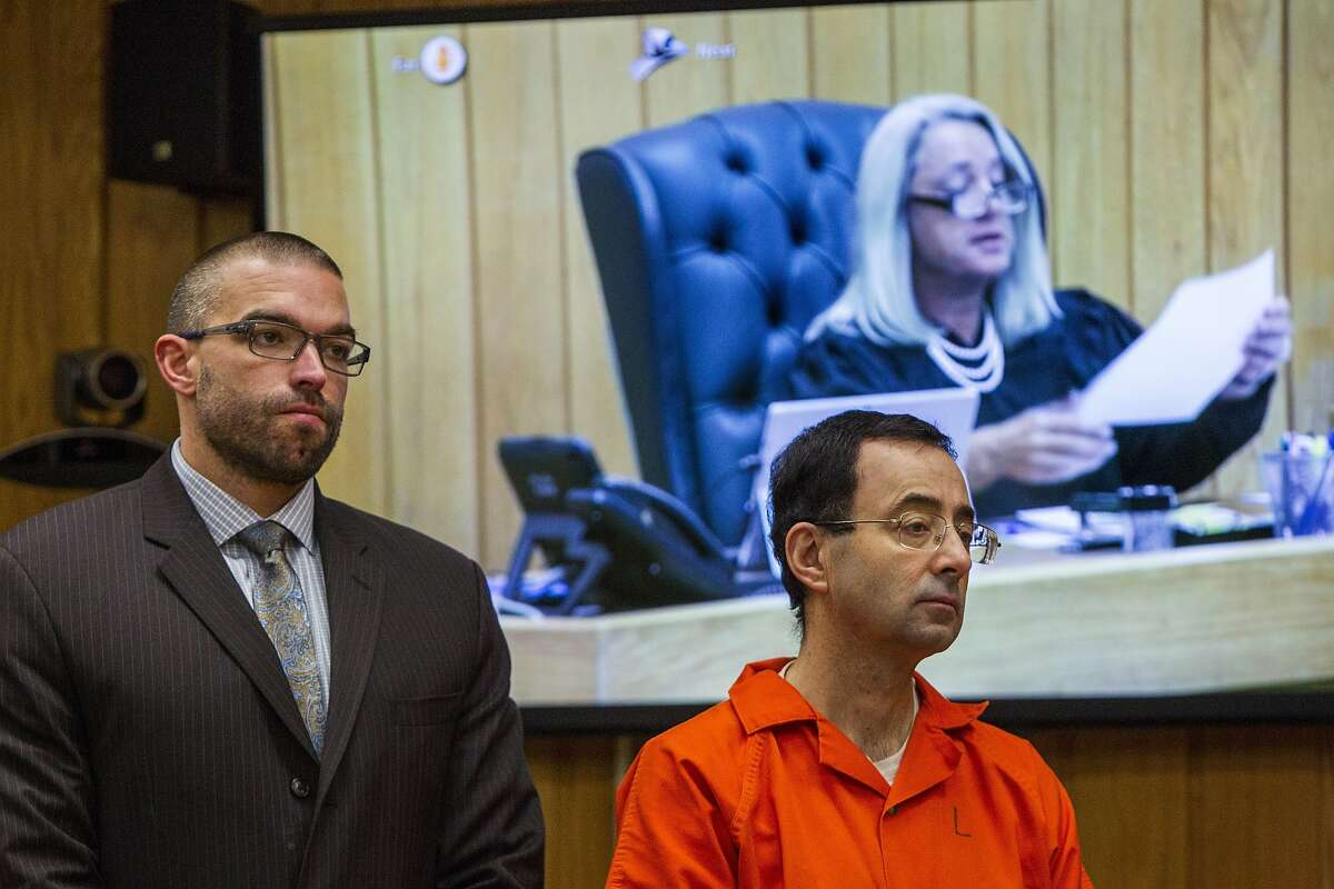 Larry Nassar, right, listens near defense attorney Matthew Newberg as Judge Janice Cunningham (pictured on the monitor) sentences Nassar at Eaton County Circuit Court in Charlotte, Mich., Monday, Feb. 5, 2018. Michigan State University has reached a $500 million settlement with hundreds of women and girls who say they were sexually assaulted by sports doctor Larry Nassar in the worst sex-abuse case in sports history.