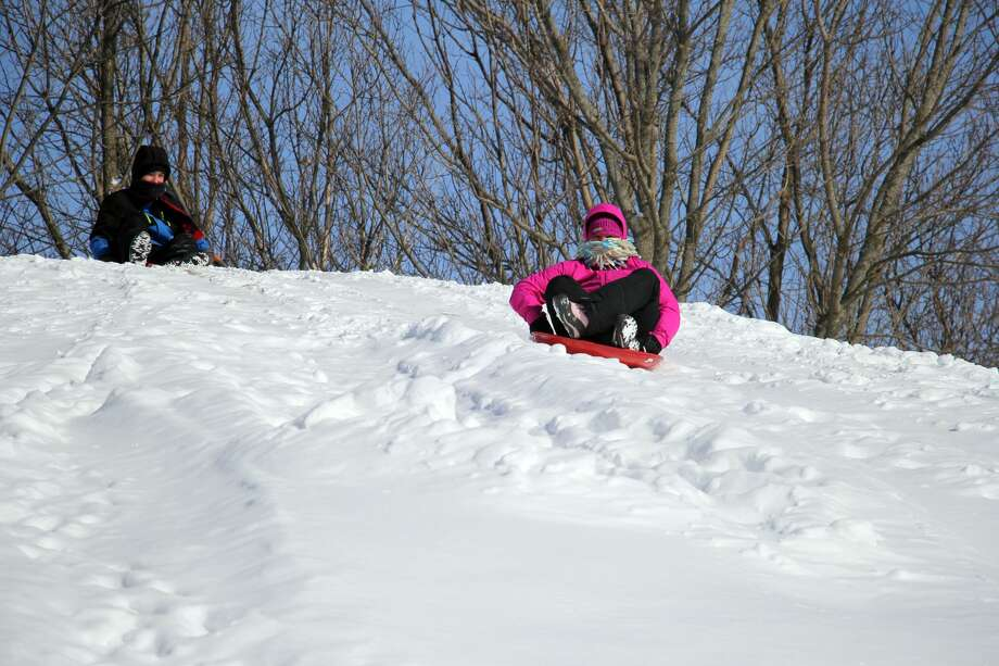 Heavy snow over the weekend cancelled schools across the county on Monday. Taking advantage of the day off were Jill and Logan Pollum, of Bad Axe. The pair braved Monday's cold temperatures to enjoy a day of sledding at Bad Axe's Wilcox Park. Photo: Seth Stapleton/Huron Daily Tribune