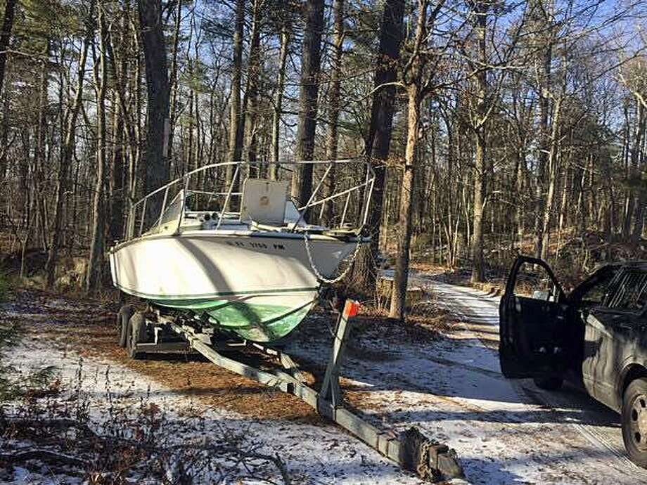 This motorboat was found abandoned in the Housatonic State Forest in Cornwall around Jan. 27. State Environmental Conservation Police are seeking the public help in solving the mystery of who owned the boat and why it was abandoned. Photo: State Environmental Conservation Police Photo