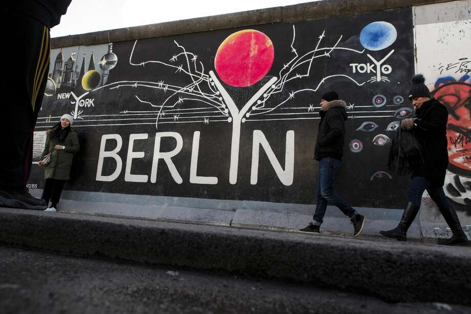 Visitors passing a painting at the Berlin Wall at the East Side Gallery on February 5, 2018 in Berlin, Germany. Photo: Carsten Koall/Getty Images