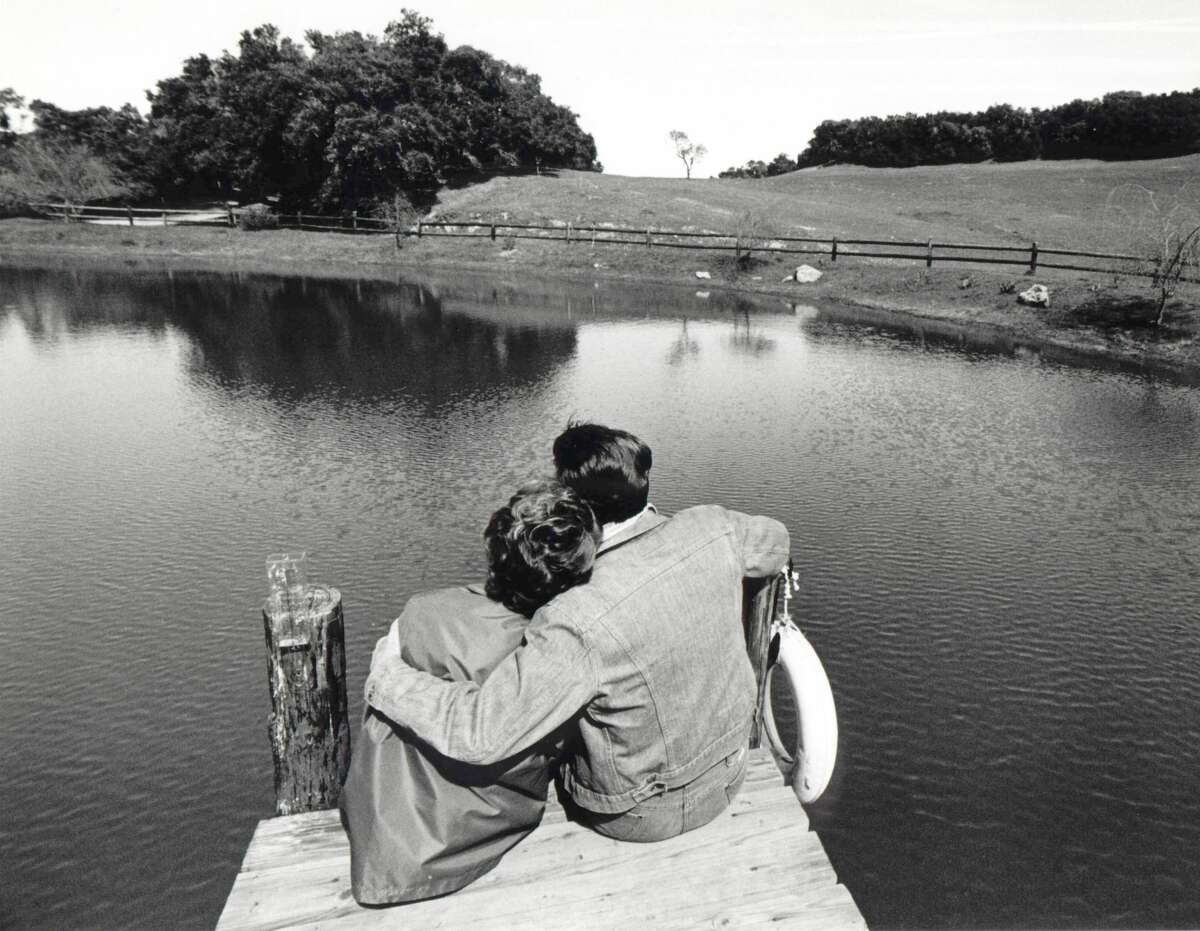 President Ronald Reagan and wife, First lady Nancy Reagan, cuddling on boardwalk facing pond at their ranch.