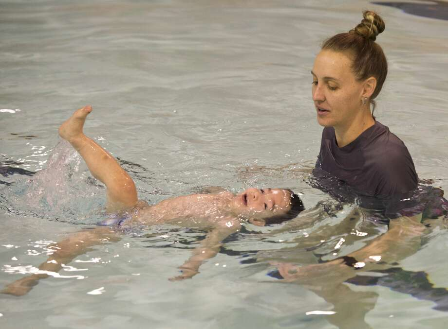 Betsy Partin works with two-year-old Rhett Meluso 02/06/18 on turning over to float on his back and learning to swim at COM. Tim Fischer/Reporter-Telegram Photo: Tim Fischer/Midland Reporter-Telegram