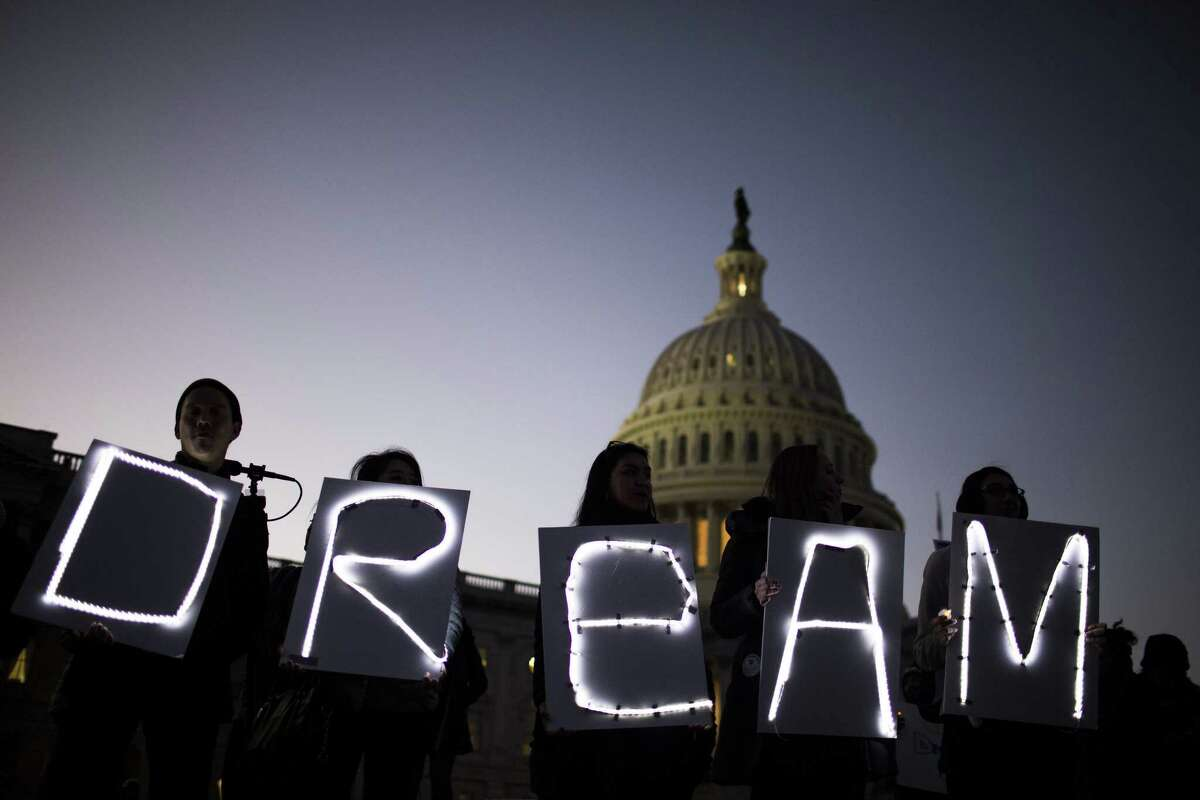 Demonstrators hold illuminated signs during a rally supporting the Deferred Action for Childhood Arrivals program (DACA), or the Dream Act, outside the U.S. Capitol building in Washington on Jan. 18, 2018.