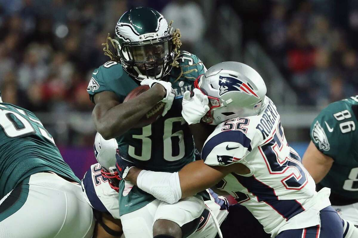 MINNEAPOLIS, MN - FEBRUARY 04: Jay Ajayi #36 of the Philadelphia Eagles runs the ball defended by Elandon Roberts #52 of the New England Patriots in the first quarter of Super Bowl LII at U.S. Bank Stadium on February 4, 2018 in Minneapolis, Minnesota.