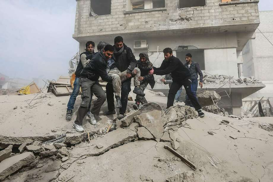 An injured man is carried after being rescued from a building that collapsed following air force strikes in the rebel-held town of Saqba near Damascus. Photo: ABDULMONAM EASSA, AFP/Getty Images