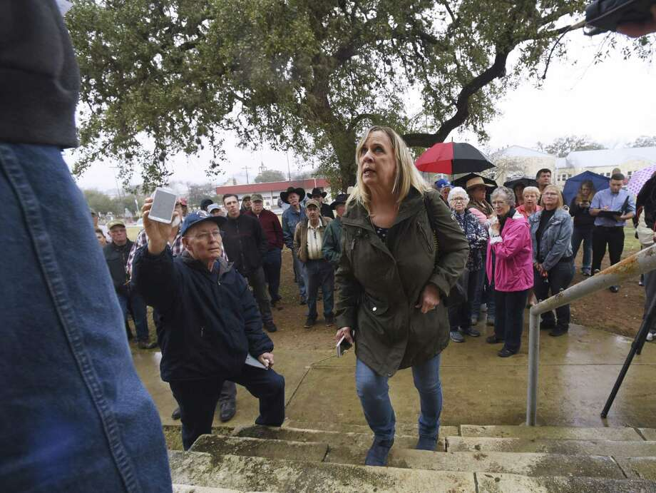 Cindy Stevens of Equalizer, Inc., approaches Dick Vetters, left, with her bid  of $3 million for the foreclosed Flying L Hill Country Resort on the Bandera County Courthouse steps on Tuesday, Feb. 6, 2018. Photo: Billy Calzada