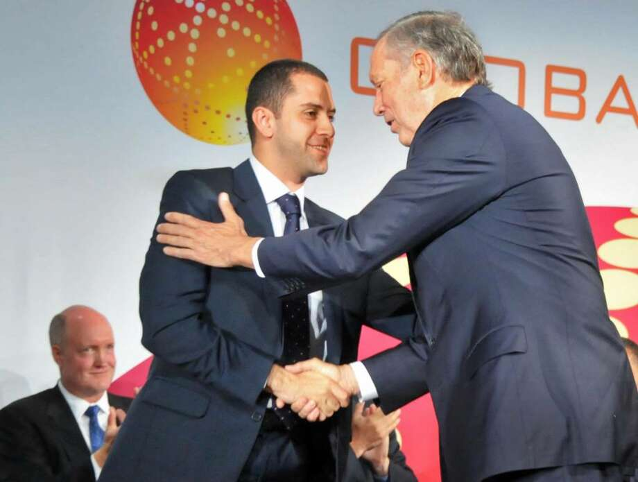 Ibrahim Ajami, chief executive officer of Advanced Technology Investment Co., an investment fund controlled by the Emirate of Abu Dhabi,left, shakes hands with former Gov. George Pataki during ground breaking ceremonies for GobalFoundries' $4.2 billion computer chip factory in Malta on Friday.    (John Carl D'Annibale / Times Union) Photo: John Carl D'Annibale / 00004795A