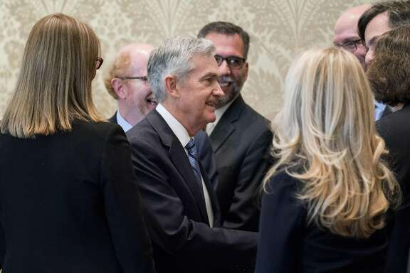 Jerome Powell, chairman of the U.S. Federal Reserve, center, shakes hands with attendees after taking the oath of office in Washington, D.C., U.S., on Monday, Feb. 5, 2018. Powell, sworn in as the 16th chairman of the Fed, is inheriting a U.S. economy in its third-longest expansion on record, with unemployment and inflation near historically low levels. Photographer: Andrew Harrer/Bloomberg