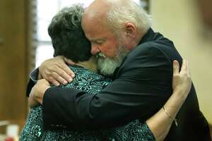 Timothy Mott, right, hugs his wife Sharlotte Mott, after she testified on the sixth day of testimony in the civil case against MPII, which does business as Mission Park Funeral Chapels and Cemeteries, accused of losing a body from a casket in 2015, in the 131st Civil District Court on Tuesday, Feb. 6, 2018.