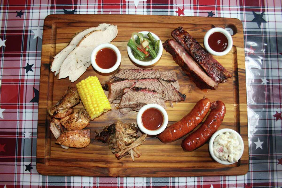 Meats from the Rusty Bucket include (clockwise from top left) smoked turkey, brisket, spare ribs, regular and jalapeño sausage and pulled pork. Side include corn on the cob, spicy green beans and macaroni salad. All meats are smoked on oak.