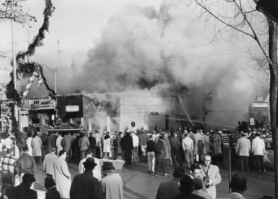1958 fire that destroyed five businesses at Main and Gordon. Hundreds of churchgoers jam Main Street to view destruction. Dow's aerial truck aids fight. Spectators carry equipment from doctor's office to safety. Smoke nearly envelops city, township firemen. December 1958 Photo: Daily News File Photo