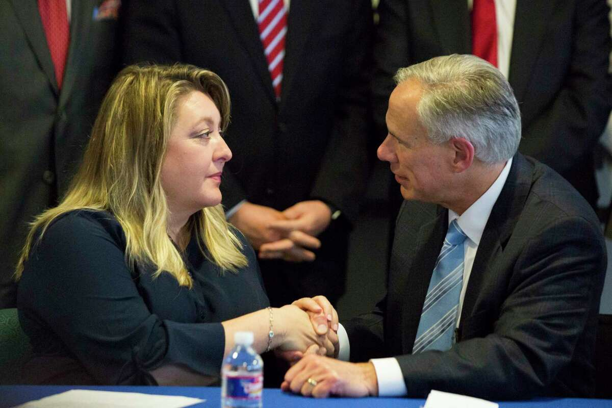 Texas Gov. Greg Abbott shakes hands with Toni McKinley, left, a sex trafficking survivor, Tuesday, Feb. 6, 2018, in Houston after a press conference.