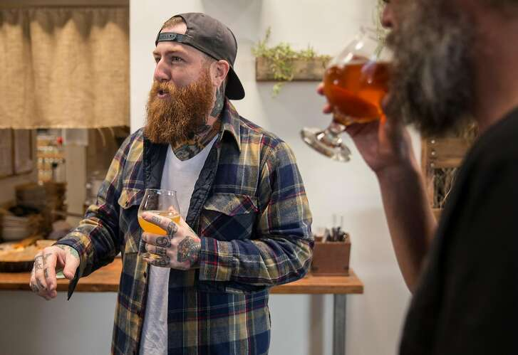 Founder Alex Tweet chats with friends while sipping beer during a special can release at Fieldwork Brewing Company Saturday, Feb. 3, 2018 in Berkeley, Calif.