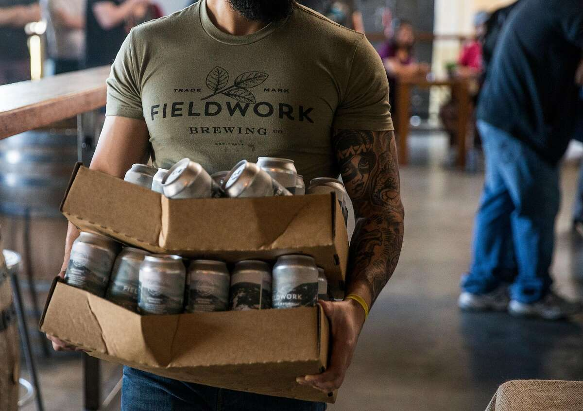 Andrew Warn carries boxes of Tundra Triple IPA to be organized for guests during a special can release at Fieldwork Brewing Company Saturday, Feb. 3, 2018 in Berkeley, Calif.