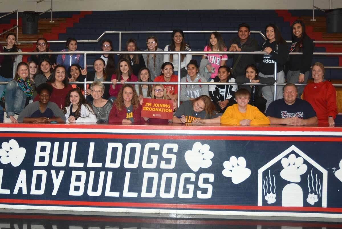 Plainview's Emily Collins, seated third from right, signs a letter of intent at the Plainview High School gym Monday to play volleyball at Division III Austin College in Sherman. Collins, a 5-foot-11 outside hitter, will major in pre-med.