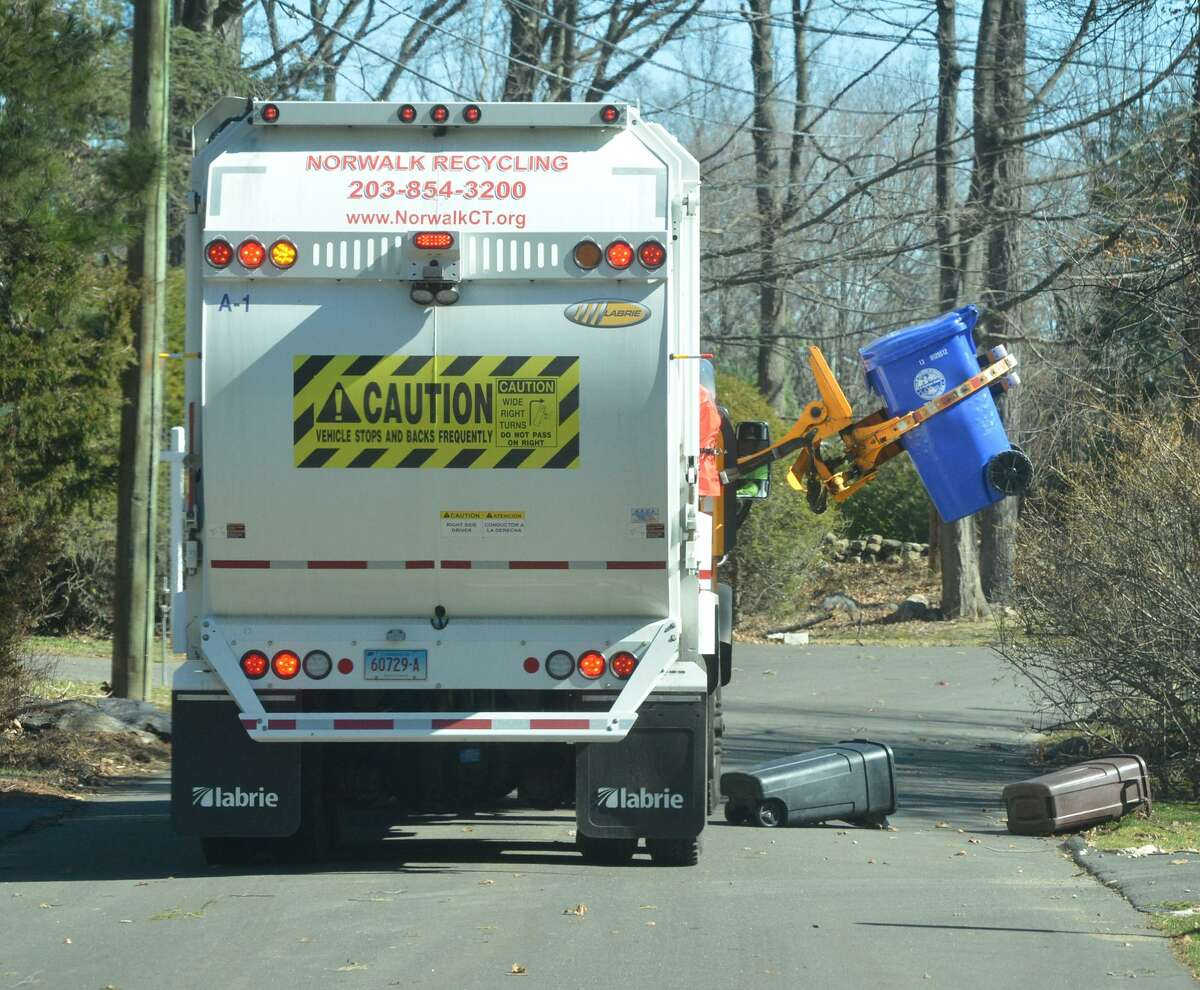 A City Carting truck picks up the recycle bins along his route in the Wolfpit section of Norwalk Conn. on Thursday March 2, 2017.