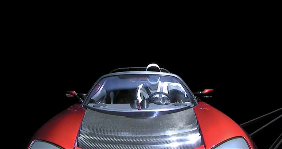 "A live video feed of various cameras inside and around the Falcon Heavy show images from space and ""Starman,"" a dummy sitting at the wheel of the Tesla roadster convertible. Photo: Courtesy SpaceX"