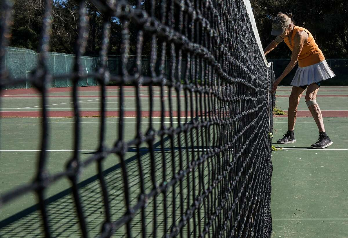Florence Barich of San Francisco retrieves the ball while playing a match with friends at the Golden Gate Park Tennis Center.