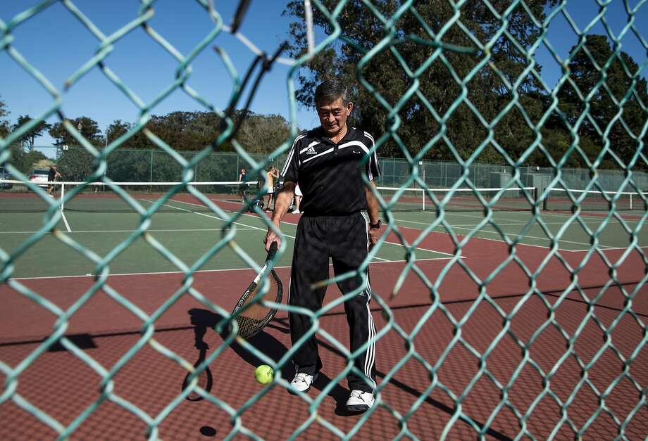 Michael Fujimoto, 73, of San Francisco is seen through a hole in the fence as he retrieves a ball while playing a match with friends at the Golden Gate Park Tennis Center. Fujimoto has been using these courts regularly for over 50 years. Photo: Jessica Christian, The Chronicle