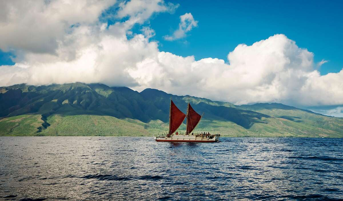 Hokule?a with open sails as she passes the south east side Molokai in the Pailolo Channel.