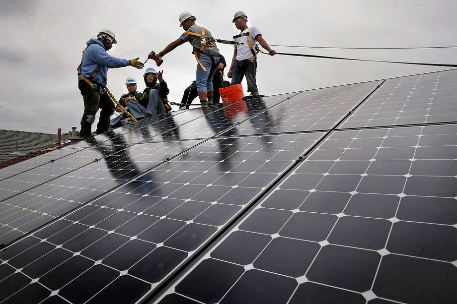 Frank Ross with Grid Alternatives, (left) works with youth from The Rising Sun Energy Center job training program as they install solar panels on the roof of a home in Richmond, Calif., as seen on Fri. May, 22, 2015. Photo: Michael Macor / The Chronicle