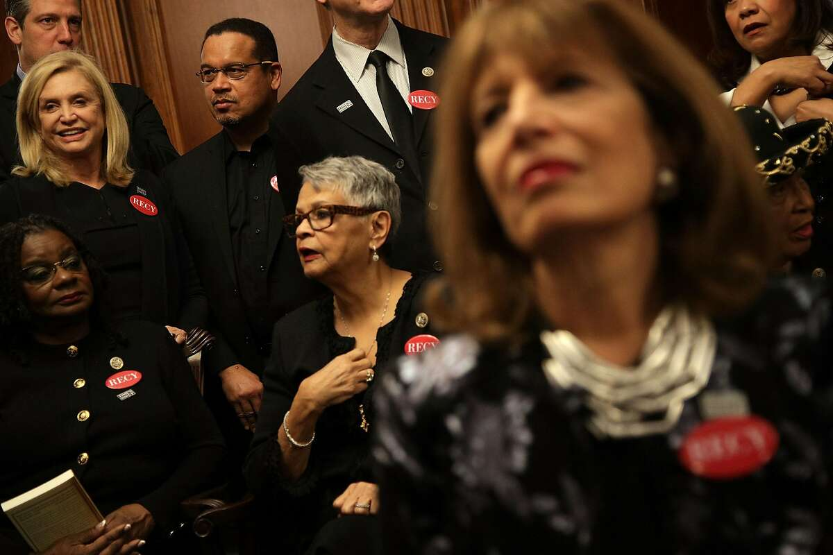 U.S. Rep. Gwen Moore, D-WI (left), Rep. Bonnie Watson Coleman, D-NJ (center), Rep. Keith Ellison, D-MN (third left), Rep. Carolyn Maloney, D-NY (second left), Rep. Jackie Speier, D-CA (right), and other House Democrats wear black as they participate in a photo-op at the U.S. Capitol prior to President Donald Trump's first State of the Union address.