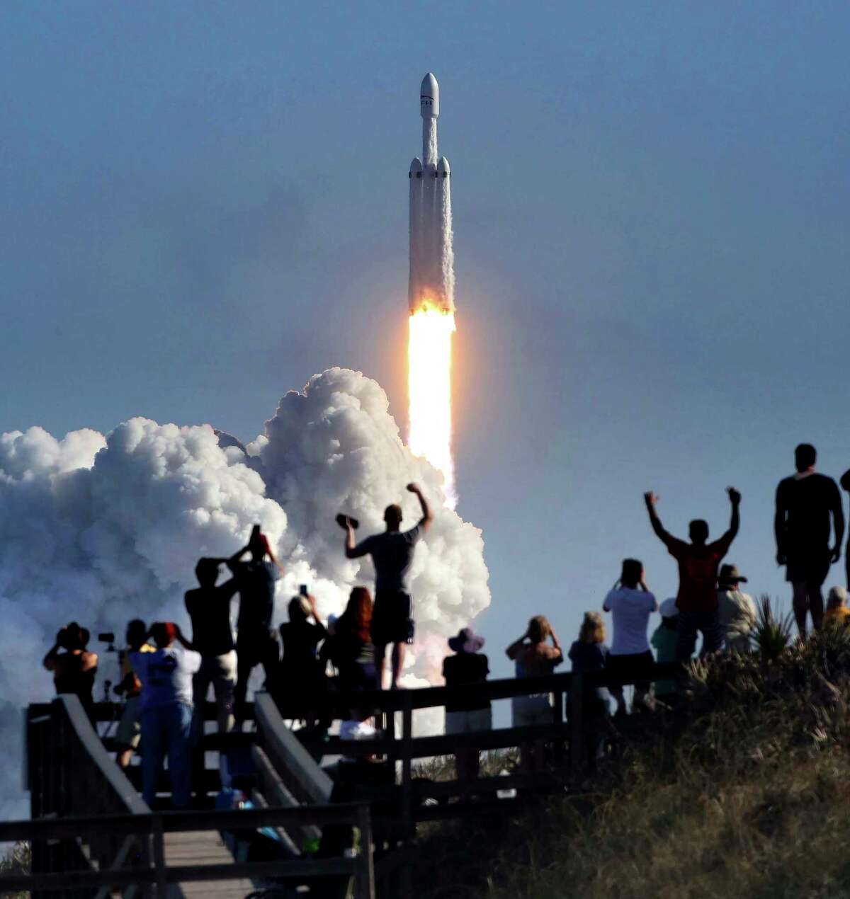 The crowd cheers the launch Tuesday of the SpaceX Falcon Heavy rocket at Cape Canaveral. The launch pad was the same one used by NASA nearly 50 years ago for the Apollo 11 moon mission.