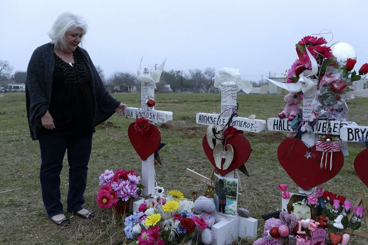 Wearing her mother's sweater, Michelle Shields touches the memorial cross for her mother, Lula Woicinski White, next to First Baptist Church of Sutherland Springs on Tuesday, Feb. 6, 2018.