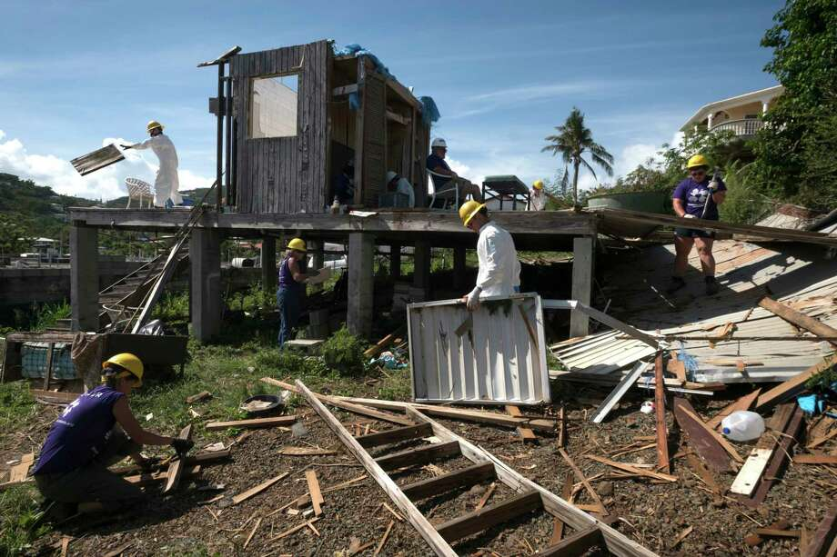 Volunteers deconstruct a storm-ravaged house in St. Thomas, in the U.S. Virgin Islands, on Jan. 22. In September, two Category 5 hurricanes damaged structures throughout the territory. Months later, many wonder where the money will come from to rebuild. Must credit: Washington Post photo by Bonnie Jo Mount Photo: Bonnie Jo Mount, The Washington Post / The Washington Post