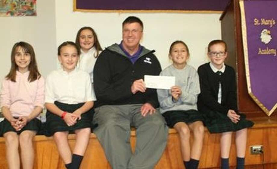 When a group of fourth- and fifth-graders from St. Mary's Academy in Hoosick Falls heard about the damage caused to their church by flooding last summer, they made rubber band bracelets and sold them to family, friends and classmates and raised about $40 on their own. They presented a check to the Rev. Tom Zelker, pastor of Immaculate Conception Church last week. (Photo provided)